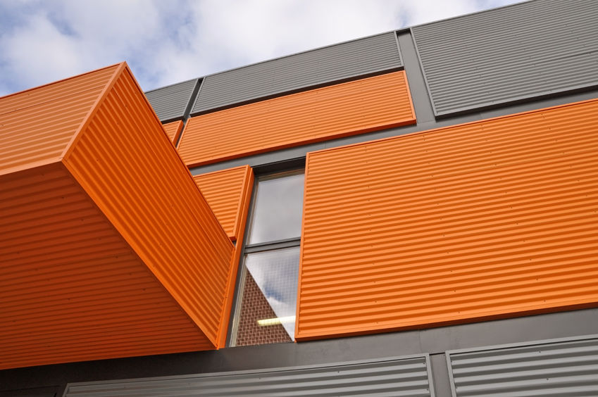 Architectural background. Wall of the modern orange and black corrugated metal panels. Look up.